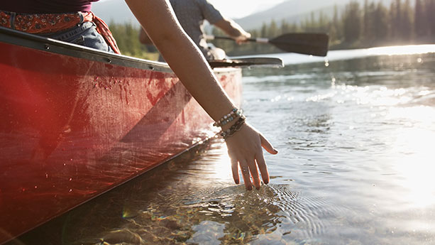 Hand in water next to canoe