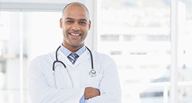 Confident ethnic male doctor smiling at camera